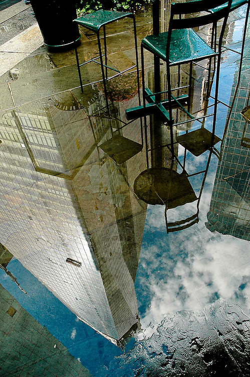 Reflection of the Bank of America tower in a puddle with chairs of a cafe in Bryant Park, Manhattan, New York, 2008.