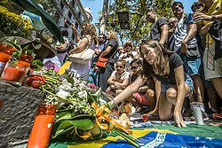 August 18, 2017 - Barcelona, Catalonia, Spain - A mourner places a candle at a makeshift memorial at Canaletas Fountains in Las Ramblas where a van ploughed through the crowds during a 550 meter long jihadist terror trip. Thirteen people were killed and almost 80 wounded, 15 seriously, when the van tore through the crowd (Credit Image: © Matthias Oesterle via ZUMA Wire)