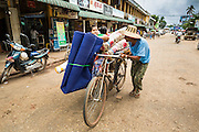 14 JUNE 2013 -  PATHEIN, AYEYARWADY, MYANMAR: A pedicab pushes a fare up the road in the market in Pathein. Pathein is a center of the Burmese umbrella and parasol industry. Most are actually parasols made in the traditional Burmese way using treated paper which is not water proof. Shwe Sar's umbrella's are made with treated cloth and are waterproof. Since US and European sanctions have been lifted businesses in Myanmar have seen an explosion in exports. Shwe Sar exports most of their umbrellas to Europe. Pathein, sometimes also called Bassein, is a port city and the capital of the Ayeyarwady Region, Burma. It lies on the Pathein River (Bassein), which is a western branch of the Irrawaddy River. It's the fourth largest city in Myanmar (Burma) about 190 km west of Yangon.   PHOTO BY JACK KURTZ