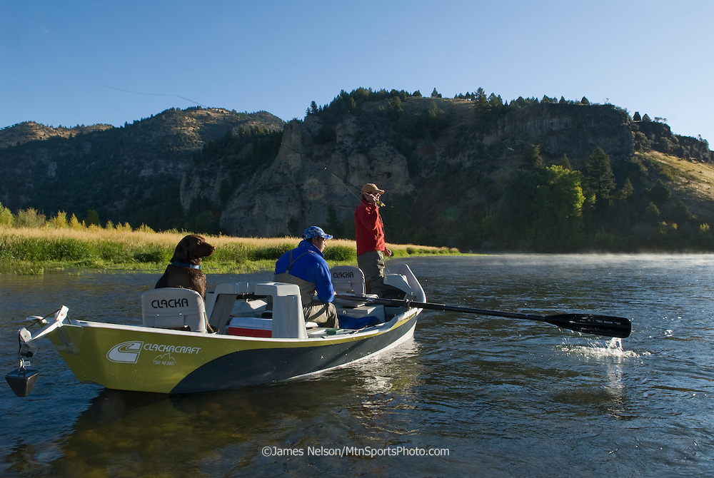 An angler in a drift boat fly fishes for trout as a chocolate Labrador retriever looks on; South Fork of the Snake River, Idaho.