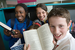 Group of Secondary School students selecting books from the library at lunch break,