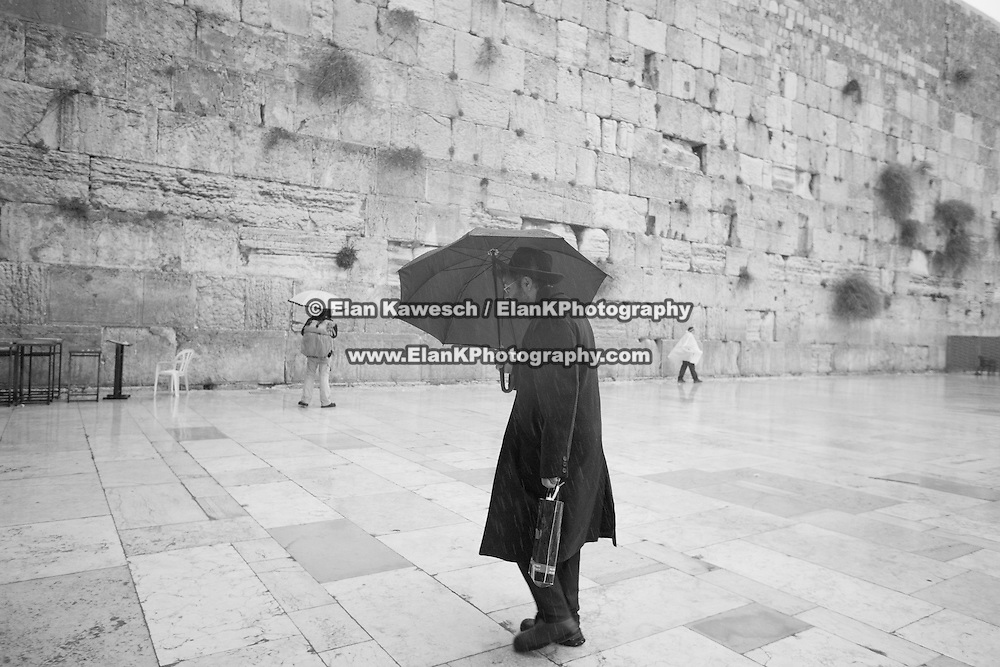 A man with an umbrella walks on the plaza as snow and rain fall at The Western Wall on January 7, 2015 in Jerusalem, Israel. (Photo by Elan Kawesch)