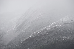 Fog envelopes snow covered mountains along the Inside Passage Lynn Canal.
