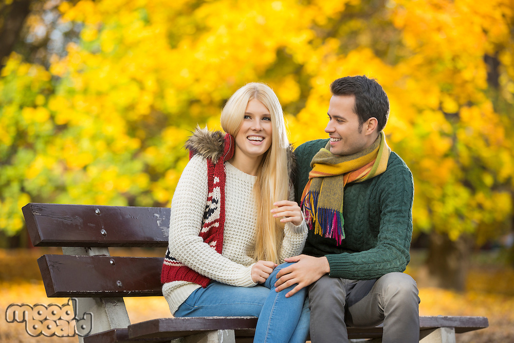 Happy young couple sitting on park bench during autumn