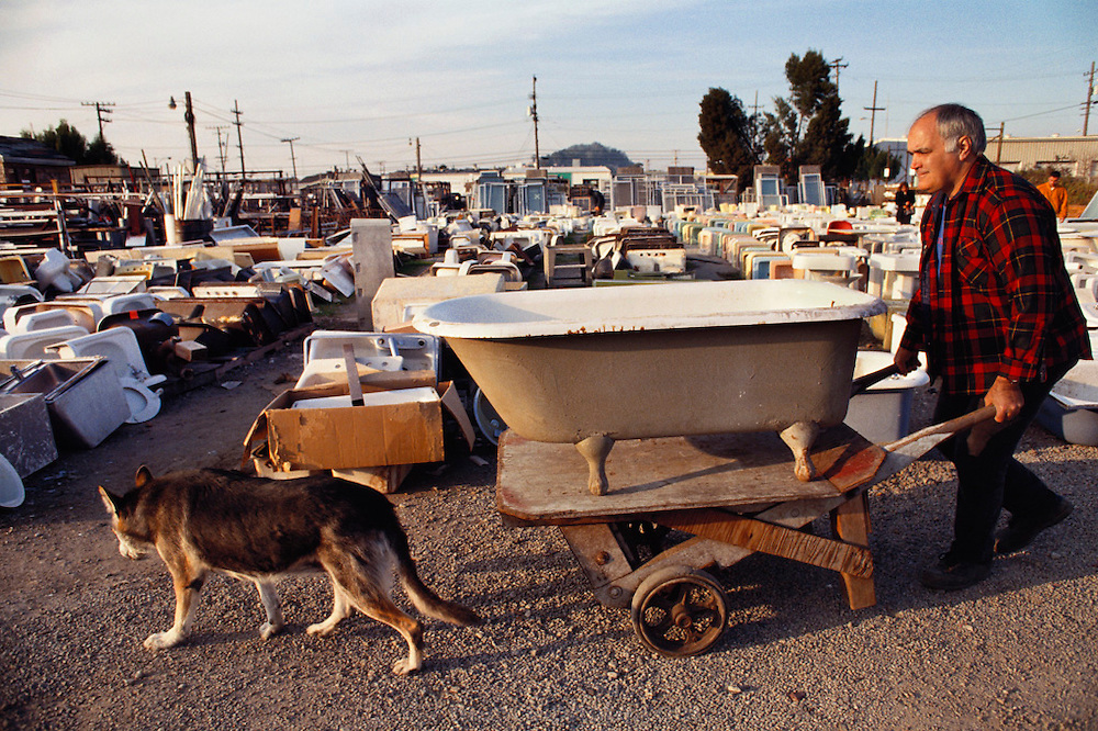 Urban Ore Recycling Company. Recycled building material and household items for sale. Don Knapp, owner with dog Sam. Berkeley, California. MODEL RELEASED. USA.