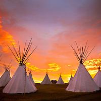 sun rising behind tepees on the blackfeet reservation