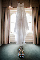 Window light illuminate this images of the bride's blue shoes and wedding gown. This image is the Bridal Suite at The Priory on Pittsburgh's North Shore.