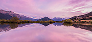 Panoramic of pink dawn over Mt Alfred and Mt Earnslaw in Glenorchy, Mount Aspiring National Park.