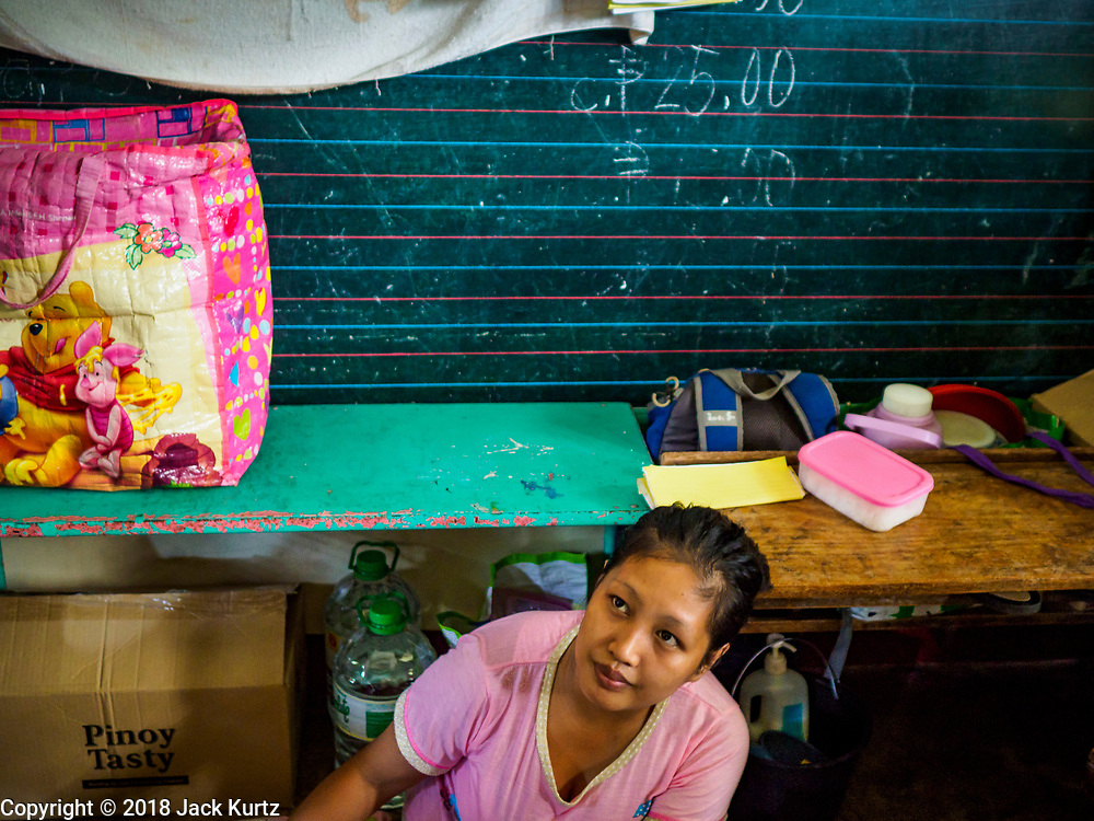 20 JANUARY 2018 - CAMALIG, ALBAY, PHILIPPINES: CRISTIN SARDALLA, sorts laundry at the Barangay Salugan evacuee shelter in a school in Camalig. There are about 870 people living at the shelter. They won't be allowed to move back to their homes until officials determine that Mayon volcano is safe and not likely to erupt. More than 30,000 people have been evacuated from communities on the near the Mayon volcano in Albay province in the Philippines. Most of the evacuees are staying at school in communities outside of the evacuation zone.  PHOTO BY JACK KURTZ