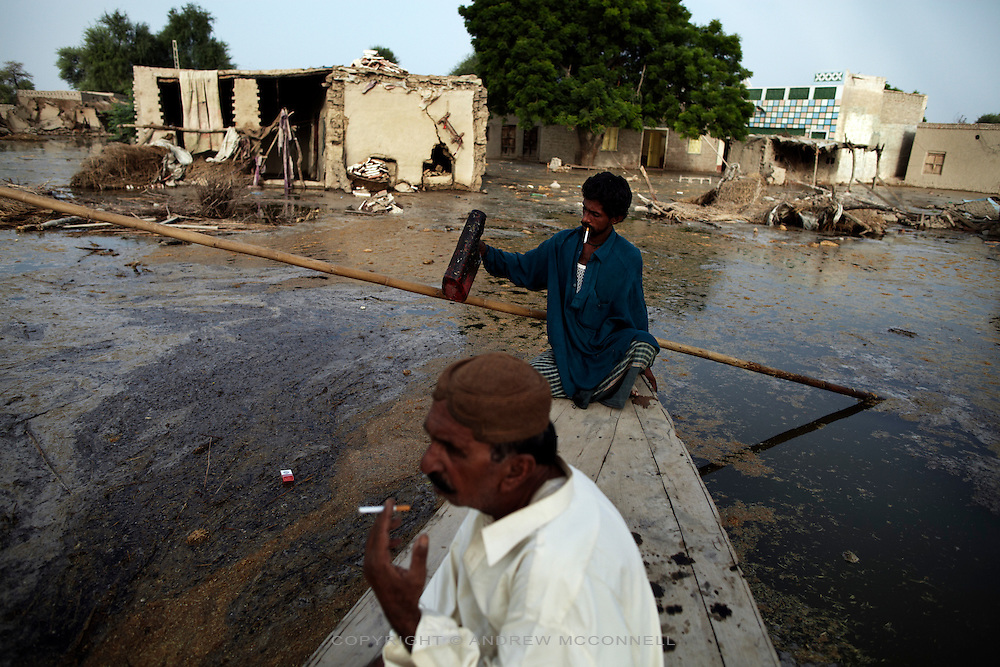 Men examine the damage to their village after floodwater swept through the area near Bubak, Sundh province, Pakistan.