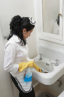 Young housemaid cleaning wash basin