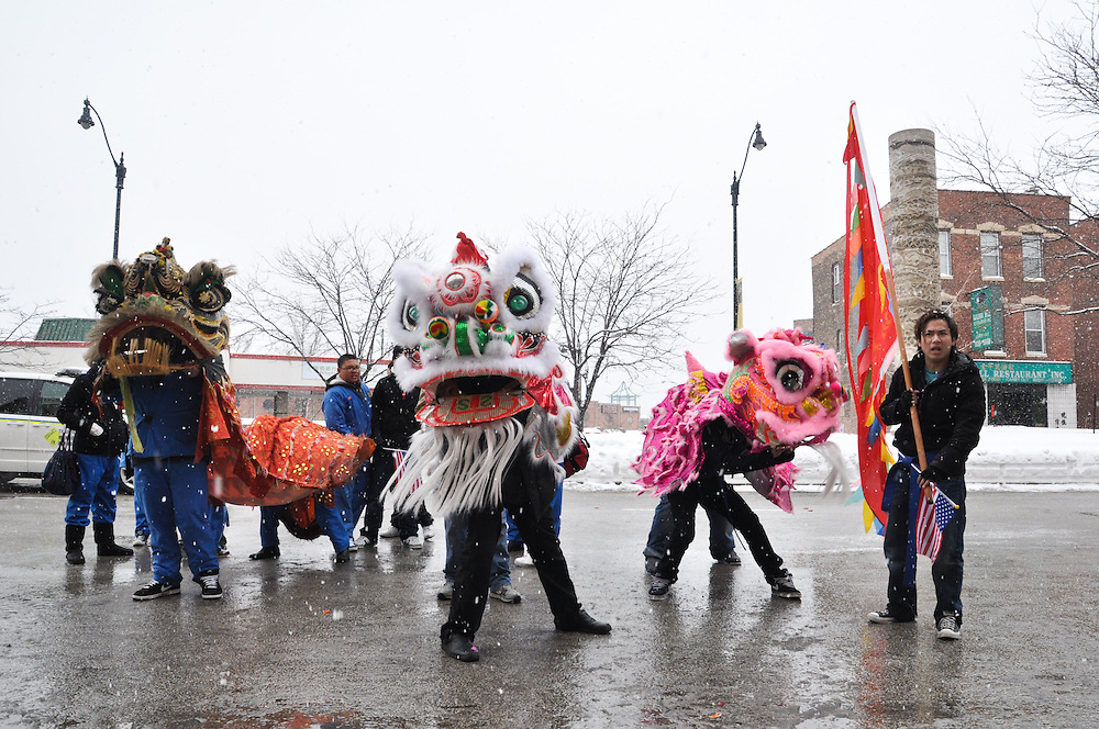 After the main parade festivities have concluded, lion dancers from the various local troupes  fan out through Chinatown to perform for local business owners, in hopes of receiving red envelopes containing monetary donations for their troupe; Chinatown, Chicago, February 6th, 2011