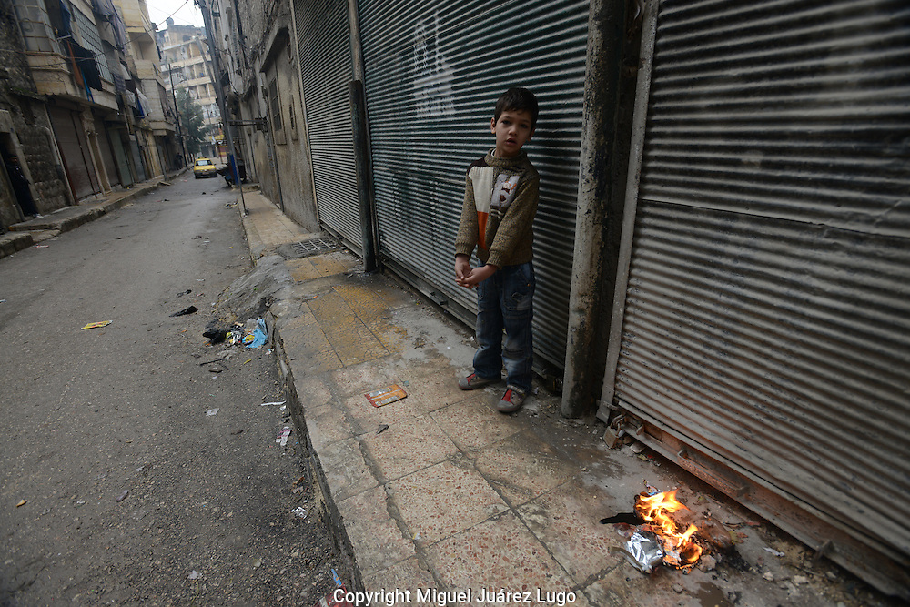 Aleppo, Syria, December, 2012. A little boy tries to keep himself warm with a small fire along a sidewalk in the Alshaar neighborhood of this city. The street is near the ruins of the Dar Al Sheffaa hospital, where more than 30 people died when the Syrian government bombed it by air almost a month ago. (Photo by Miguel Juárez Lugo)