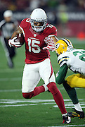 Arizona Cardinals wide receiver Michael Floyd (15) gives a straight arm on a tackle attempt by Green Bay Packers rookie cornerback Damarious Randall (23) as he looks for yards after a catch on a 9 yard pass completion that gives the Cardinals a first down at the Green Bay Packers 34 yard line on a third down play in the fourth quarter during the NFL NFC Divisional round playoff football game against the Green Bay Packers on Saturday, Jan. 16, 2016 in Glendale, Ariz. The Cardinals won the game in overtime 26-20. (©Paul Anthony Spinelli)