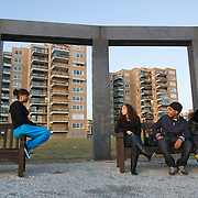 Nederland Rotterdam 27 september 2009 20090927 ..Allochtone jongeren zitten buiten op een bankje te chillen, praten met elkaar en vermaken zich, op de achtergond woontorens. .Youth chilling  outside, in the neighbourhood.        .                           .Foto: David Rozing