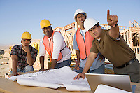 Four construction workers examining blueprints on construction site