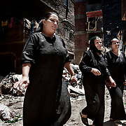 """Mujeres """"Zabbaleen"""" en el barrio de Mokattam . En medio del barrio de Manshiet Nasr a las afueras de El Cairo esta situado el asentamiento de Mokattam conocido como la """"Ciudad de la Basura"""" , está habitado por los Zabbaleen ,una comunidad de unos 45.000 cristianos coptos que viven desde hace varias décadas de reciclar los desperdicios que genera la capital egipcia: plástico, aluminio, papel y desechos órganicos que transforman en compost . La mayoría forman parte de la Asociación para la Protección del Ambiente (APE) una ONG que actúa en el área, cuyos objetivos son proteger el medio ambiente y aumentar el sustento de las recuperadores de basura de El Cairo. Según la ONU, el trabajo que se realiza en Mokattam como uno de los diez mejores ejemplos del mundo en el mejoramiento medioambiental. El Cairo , Egipto, Junio 2011. ( Foto : Jordi Camí )"""