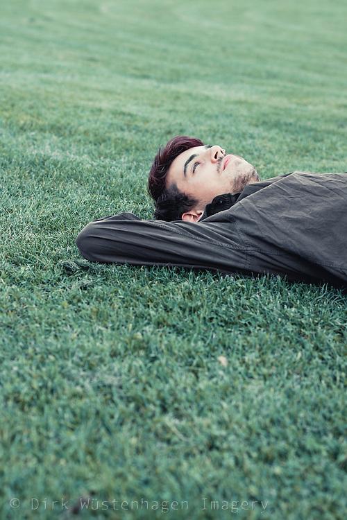 Auf Rasen liegender junger Mann, Wuppertal, Deutschland