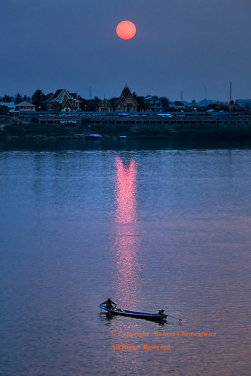 Mekong Red: A fisherman collects his line in the late evening light as a late red sun casts its light upon the Mekong River, Thakhek Laos.