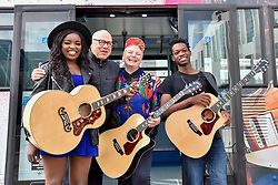 © Licensed to London News Pictures. 21/07/2017. London, UK. Dire Straits frontman Mark Knopfler unveils two iconic London buses outside Wembley Stadium to celebrate launch of Gigs, in association with Gibson, on the eve of International Busking Day. Mark Knopfler stands with musicians (L to R) Modupe Obasola, Kal Lavelle and Jay Johnson whose pictures are featured on the buses and who have all taken part in the Mayor of London's annual busking competition.    Photo credit : Stephen Chung/LNP