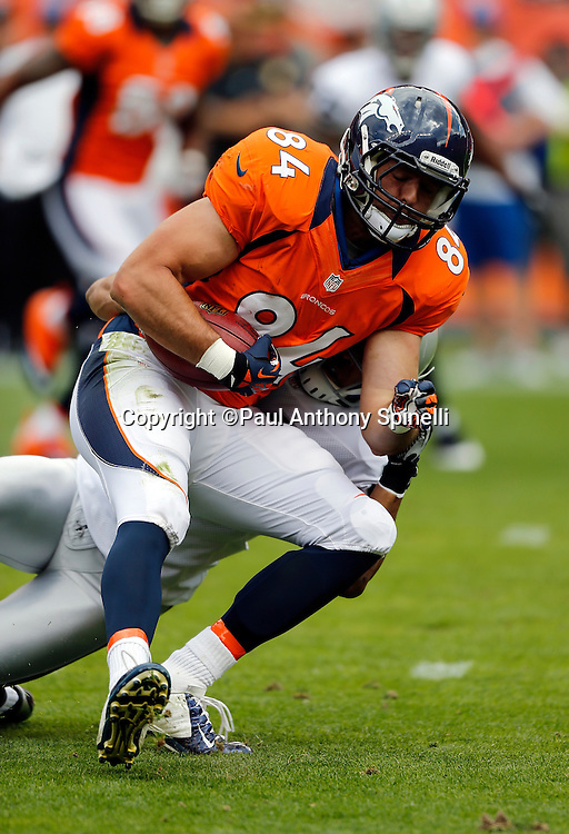 Denver Broncos tight end Jacob Tamme (84) gets tackled after catching a first quarter pass good for a first down during the NFL week 4 football game against the Oakland Raiders on Sunday, Sept. 30, 2012 in Denver. The Broncos won the game 37-6. ©Paul Anthony Spinelli