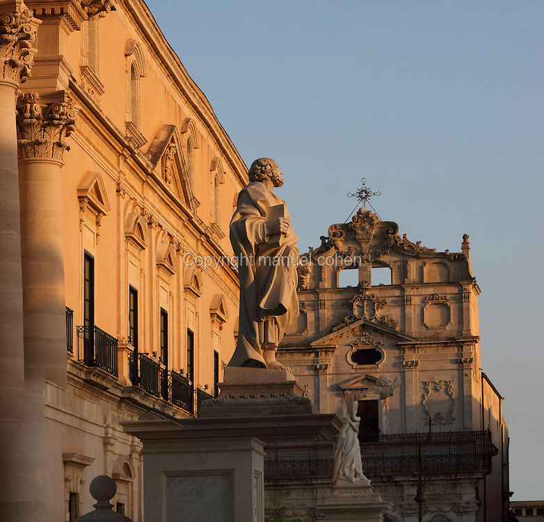 Syracuse cathedral (left) or Duomo, rebuilt in the 18th century and right, the Chiesa di Santa Lucia all Badia, or Church of St Lucy, a Baroque church dedicated to the virgin martyr from Syracuse and patron saint of the city, Ortygia Island, Syracuse, Sicily, Italy. The statue is of St Peter, holding a key and a book. The island is also known as the Citta Vecchio, as it is the old town of Syracuse and contains many historical buildings. Syracuse was founded in 734 BC and was a thriving city in ancient Greek times, and the birthplace of Archimedes. Much of Syracuse was rebuilt after the earthquake of 1693 and the Sicilian Baroque style is therefore prevalent. The old town of Syracuse is listed as a UNESCO World Heritage Site. Picture by Manuel Cohen