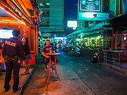 "22 MAY 2014 - BANGKOK, THAILAND: A foreigner drinks a beer at a bar on Soi Cowboy, one of Bangkok's ""adult entertainment"" districts, after the Thai army announced an overnight curfew. The Thai army suspended civilian rule, suspended the constitution and declared the ""military takeover of the nation."" The announcement came just before evening as a meeting between civilian politicians and the army was breaking up with no progress towards resolving the country's political impasse. Civilian politicians were arrested when the meeting ended. The army also declared a curfew from 10PM until 5AM.    PHOTO BY JACK KURTZ"