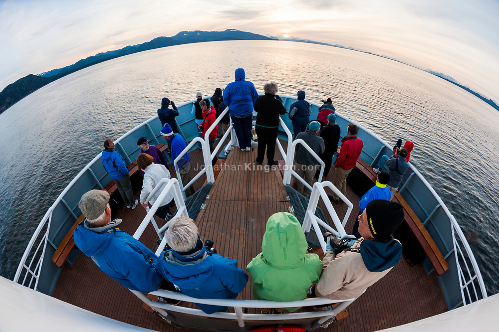Passengers on the bow of a cruise ship watch the sun set in Alaska.