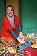 Asma Yunidar packaging up her cakes to sell in the market.<br /> <br /> Asma runs her own snack business, making pasties, donuts, crisps and other snacks from her small home kitchen. <br /> <br /> After attending the business training she learnt how to keep her books accurately and she has now realised she earns more than her husband.