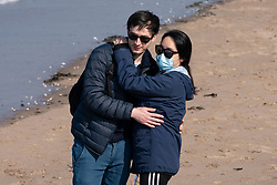 Portobello, Scotland, UK. 25 April 2020. Views of people outdoors on Saturday afternoon on the beach and promenade at Portobello, Edinburgh. Good weather has brought more people outdoors walking and cycling. The beach appears busy with possibly a breakdown in social distancing happening later in the afternoon. Young couple embracing on the beach, asian female wearing a face mask. Iain Masterton/Alamy Live News