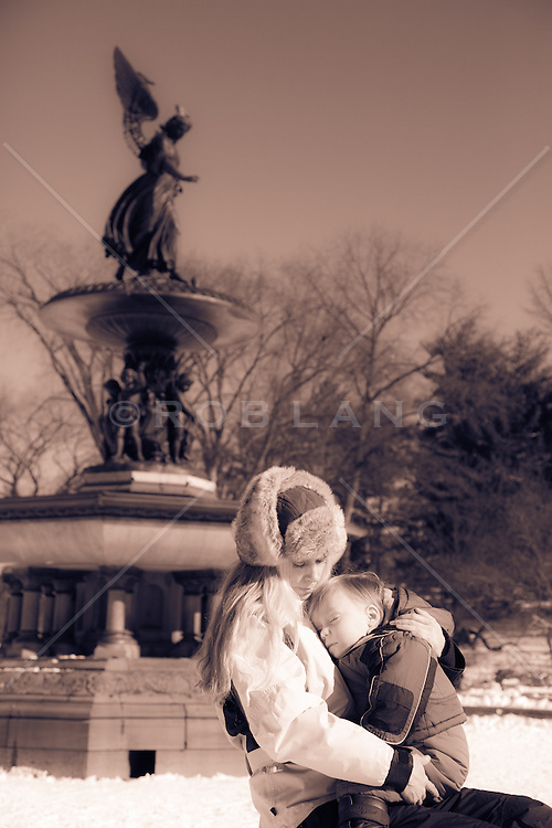 woman and baby sitting together by the Bethesda Fountain in Central Park in the Winter