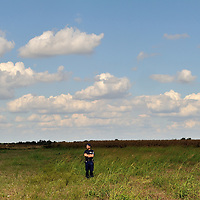 An Hungarian policeman standing in a field, one of a score of officers ringed around a field near Röszke, where refugees and migrants are being held prior to enforced registration.  The official border reception centres are full and refugees must camp on the ground, dependent mostly on food donated by volunteer groups