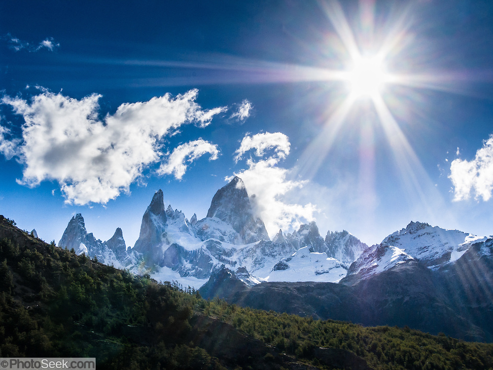 "Sun with lens flares over Mount Fitz Roy (3405 meters or 11,170 feet) in the southern Andes mountains, near El Chaltén village, in Los Glaciares National Park, Argentina, South America. Bright sun creates lens flares shining through a stopped down camera aperture. In 1877, explorer Perito Moreno named ""Cerro Fitz Roy"" for Robert FitzRoy (no space before the capital R) who, as captain of the HMS Beagle, had travelled up the Santa Cruz River in 1834 and charted much of the Patagonian coast. First climbed in 1952 by French alpinists Lionel Terray and Guido Magnone, Mount Fitz Roy has very fickle weather and is one of the world's most challenging technical ascents. It is also called Cerro Chaltén, Cerro Fitz Roy, and Monte Fitz Roy (with a space before the R). Chaltén comes from a Tehuelche (Aonikenk) word meaning ""smoking mountain"" (explained by frequent orographic clouds). Cerro is a Spanish word meaning hill. El Chaltén village was built in 1985 by Argentina to help secure the disputed border with Chile, and now tourism supports it, 220 km north of the larger town of El Calafate. The foot of South America is known as Patagonia, a name derived from coastal giants, Patagão or Patagoni, who were reported by Magellan's 1520s voyage circumnavigating the world and were actually Tehuelche native people who averaged 25 cm (or 10 inches) taller than the Spaniards. Mount Fitz Roy is the basis for the Patagonia company's clothing logo, after Yvon Chouinard's ascent and subsequent film in 1968."