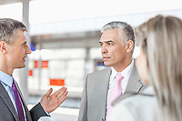 Businessman communicating with colleagues on railroad platform
