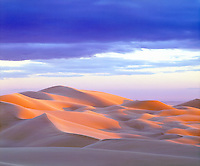 The perfect photograph of the Glamis Sand Dunes at sunset that contrasts the dark storm clouds against the soft glowing sand.
