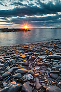 Looking out over Saco Bay at sunset from the rocky shoreline of Stratton Island, Maine.