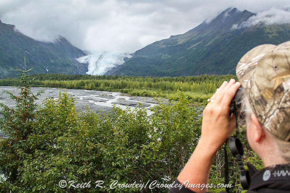 A visitor uses binoculars to get a better look at a glacier near Seward, Alaska.