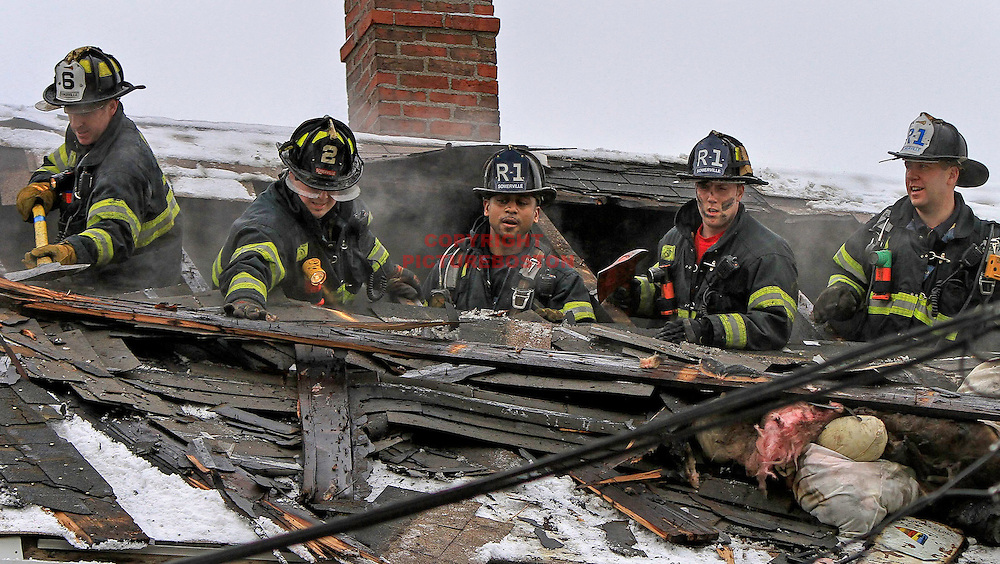 Somerville,MA firefighters work at 48 Glen St. in that city this morning, March 2, 2012, after a 2-alarm fire caused significant damage to the occupied home. Photo: Mark Garfinkel/Boston Herald