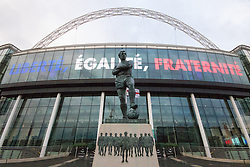 Wembley Stadium, London, November 17th 2015. Hours befor kick-off French and England fans begin to gather outside Wembley Stadium as both England and France national teams are poised to play in an emotional tie just days after the tragic death of 130 people in the Paris Islamist attacks. PICTURED:  Sir Bobby Moore watches over Wembley Park as the French National motto illuminates the walls of Wembley. // Licencing Contact: paul@pauldaveycreative.co.uk Mobile 07966 016 296