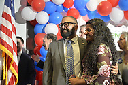 Garden City, New York, USA. November 6, 2018. Nassau County Democrats watch Election Day results at Garden City Hotel, Long Island. KEVIN THOMAS was elected New York State Senator for 6th District. His wife RINCY is standing next to him.