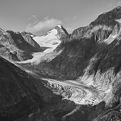 The Aletsch Glacier (German: Aletschgletscher) or Great Aletsch Glacier (German: Grosser Aletschgletscher) is the largest glacier in the Alps. It has a length of about 23 km (14 mi) and covers more than 120 square kilometres (46 sq mi) in the eastern Bernese Alps in the Swiss canton of Valais. The Aletsch Glacier is composed of three smaller glaciers converging at Concordia, where its thickness is estimated to be near 1 km (3,300 ft). It then continues towards the Rhone valley before giving birth to the Massa River.<br />