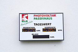 Display panel on exterior wall showing energy produced by solar panels on modern highly energy efficient family house  in Germany