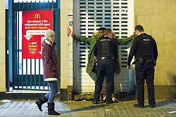 """© Licensed to London News Pictures . 15/12/2017. Manchester, UK. Police stop and search a man outside McDonalds in Piccadilly Gardens . Revellers out in Manchester City Centre overnight during """" Mad Friday """" , named for historically being one of the busiest nights of the year for the emergency services in the UK . Photo credit: Joel Goodman/LNP"""