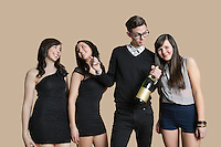 Portrait of mid adult man and young females holding champagne bottle over colored background