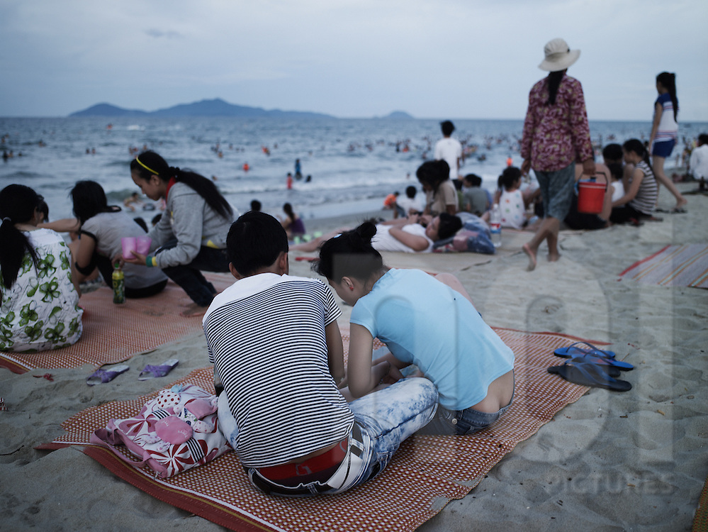 A vietnamese couple have a picnic on the beach along the shore of Hoi An, Vietnam, Asia