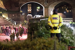 "© Licensed to London News Pictures . 03/11/2017 . Manchester , UK . Police watch on as fans of Tommy Robinson (real name Stephen Yaxley-Lennon ) queue for signed books at the launch of the former EDL leader's book "" Mohammed's Koran "" at Castlefield Bowl . Originally planned as a ticket-only event at Bowlers Exhibition Centre , the launch was moved at short notice to a public location in the city . Photo credit : Joel Goodman/LNP"