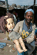 "ADDIS ABABA, ETHIOPIA..The ""Mercato"", biggest market between Cairo and Cape Town. Man selling white-skinned doll..(Photo by Heimo Aga)"