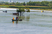 Chinese fishermen fish in a lake near the Old Town of Lijiang, Yunnan, China