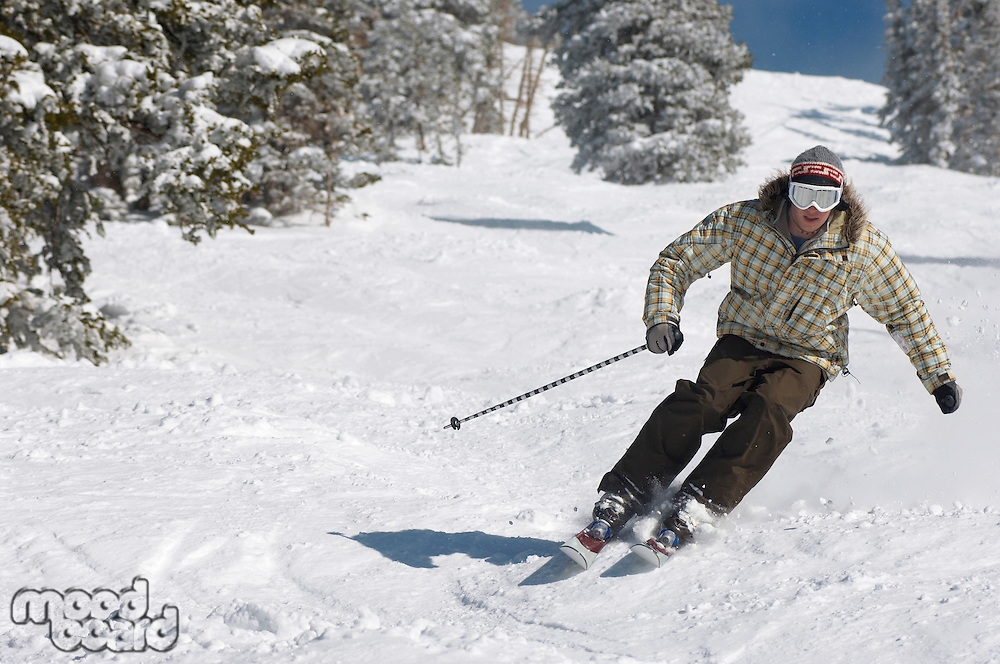 Young Man Skiing down snow covered slope full length