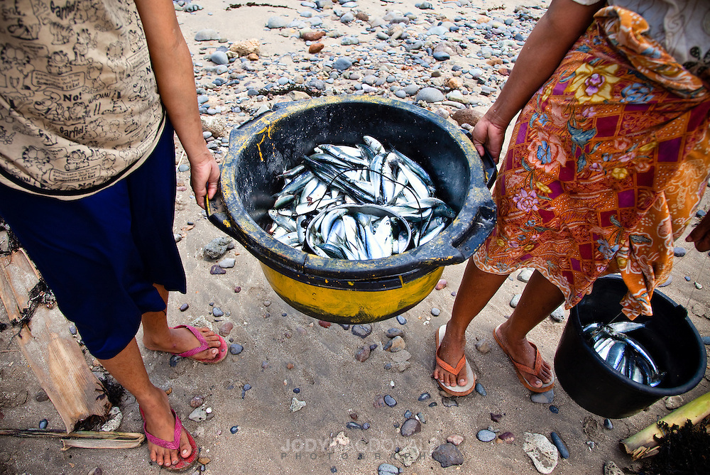 Two women carry a basket of small freshly caught fish to sell at the local market in Lakey, Sumbawa, Indonesia.